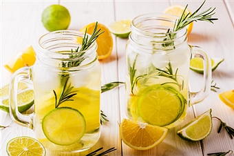 Homemade lemonade with lime, lemon, rosemary in  mason jar on  wooden white background.